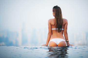 summer vacation travel photo - beautiful young perfect sexy body and skin wet girl in white bikini swimming and standing on the edge of pool on the top of hotel and looking in a city panorama