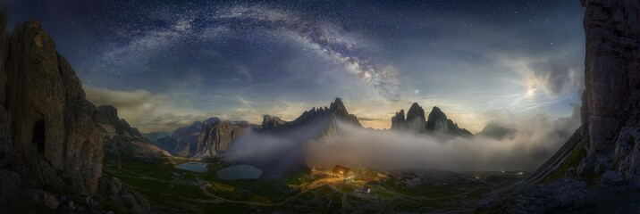 Beautiful panoramic shot of a mountain valley with a small illuminated house under the starry sky Fototapete