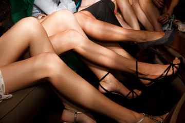 Line of girls' legs on high heels sitting in limo during bachelorette party or a birthday, a group of bridesmaids having fun.