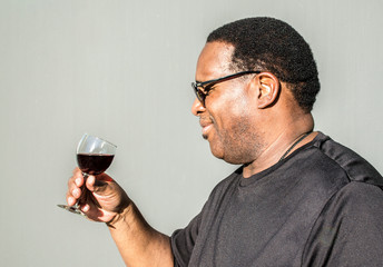 profile of a middle aged African American man holding a glass of red wine against a solid background with copy space