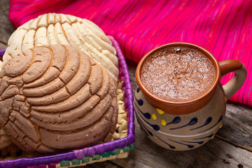 Foto auf Leinwand Schokolade Mexican hot chocolate with sweet conchas bread on wooden background
