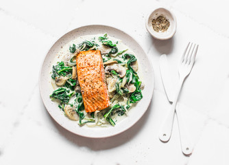 Roasted salmon with creamy spinach mushrooms sauce on a light background, top view. Salmon florentine