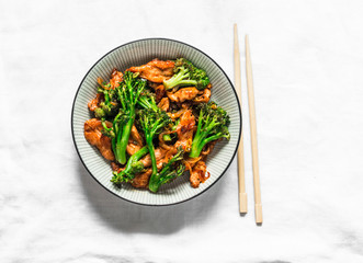 Teriyaki stir fry chicken with broccoli and noodles on light background, top view. Asian style food