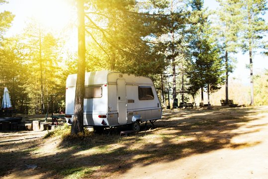 Campsite . Caravan car parking with old style vans. Family vacation travel, holiday trip in motorhome . Caravan trailer on a green lawn at the camping