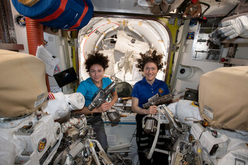 U.S. astronauts Jessica Meir and Christina Koch pose in the International Space Station