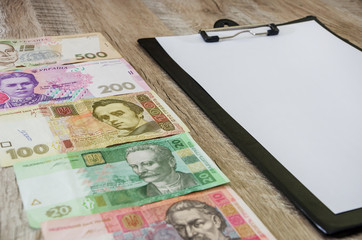 Ukrainian money and a white sheet of paper on the table. Place for text.