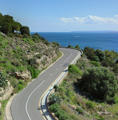 Coastal road on Ibiza with blue sky and sea in the background