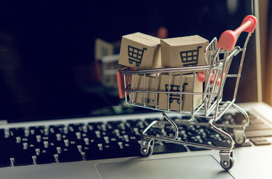 Shopping online. cardboard box with a shopping cart logo in a trolley on a laptop keyboard. Shopping service on The online web. offers home delivery..