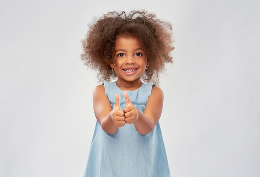 childhood, gesture and people concept - happy little african american girl showing thumbs up over grey background