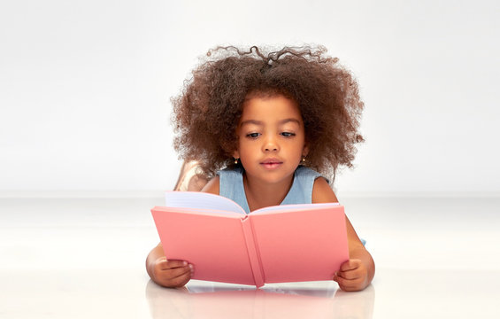 childhood, school and education concept - little african american girl reading book over grey background