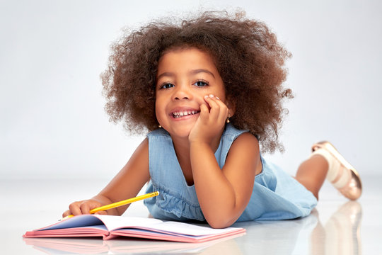 childhood, creativity, drawing and people concept - happy little african american girl with sketchbook and pencil over grey background