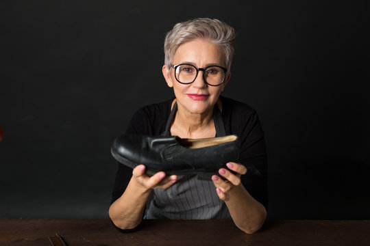 stylish aged woman in glasses on a black background with a boot in her hands