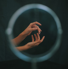 Two gesturing hands reflected in circular mirror