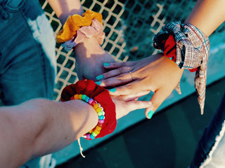 Three hands with bracelets overlapping