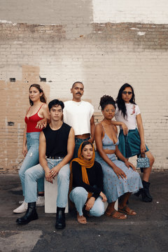 Portrait of group of friends pose outside by brick wall