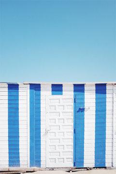 Blue and white vertical striped beach hut