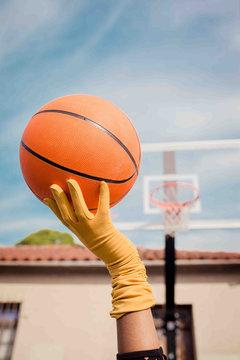 Gloved hand balancing basketball on fingertips