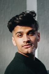 Portrait of man with vitiligo, black hair, and green eyes