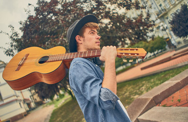 Young man walk at street with guitar. Stylish hipster guy enjoys music and holidays.