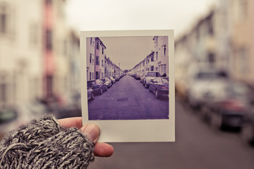 Woman holding picture of street in her hands