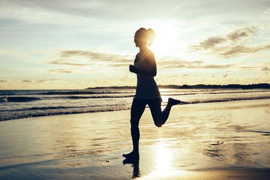 Fitness woman runner running on sunset beach