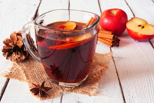 Autumn spiced tea with apples and cinnamon. Side view on a white wood background.
