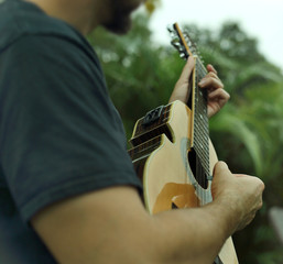 A puerto rican man playing the cuatro. A Puerto Rico national string instrument.