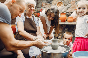 Family make a small jug. Hands of a potter at work.