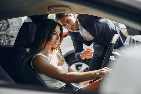 Couple in a car salon. Family buying the car. Elegant woman with her boyfriend