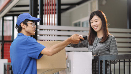 Delivery man shipping parcel to his Customer at home, Customer Signature on Smart phone