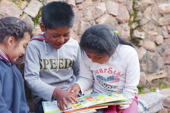 Native american kids reading a  book.