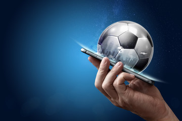 Smartphone in hand with a 3D soccer ball on a blue background. Bets, sports betting, bookmaker. Mixed media