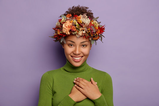 Candid shot of attractive smiling woman feels thankful, promises be loyal, appreciates pleasant gift, touches chest gratefully, wears autumn wreath, values somebodys offer, poses indoor in casual wear