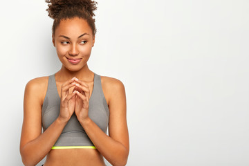 Sport and active lifestyle concept. Healthy slim woman in sport clothes, keeps hands togeter, has intention to do something, looks thoughtfully aside, poses against white studio wall, blank space