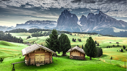 Small wooden huts at sunrise in Alpe di Siusi, Dolomites