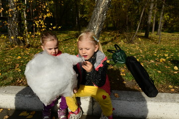 Mom with her beautiful daughters eats cotton candy and puffs in the park