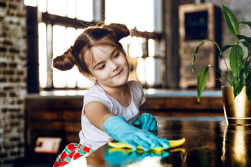 A beautiful little girl in rubber gloves does the cleaning, rags the dust from the table. Helps mom.