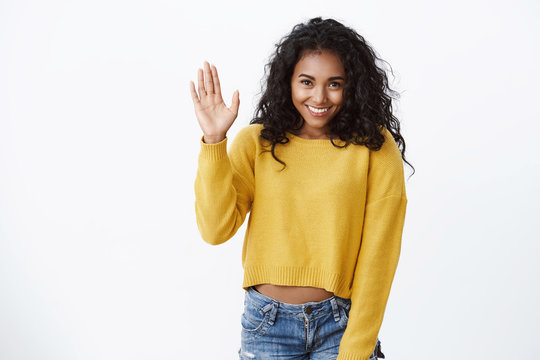 Shy lovely african-american girl in yellow sweater, curly hairstyle, stooping as raising hand, waving hello, hi gesture, smiling, modest woman introduce herself in front audience, white background