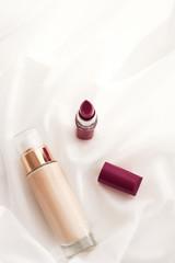 Beige tonal cream bottle make-up fluid foundation base and dark lipstick on silk background,...