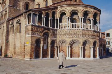 ヴェネツィアのムラーノ島のサンタ・マリア・エ・ドナート教会を背景に歩く老人