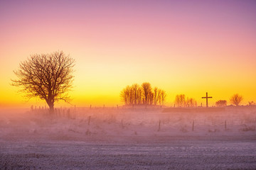 Fotobehang Oranje Sunset and cold mist in a wintry landscape