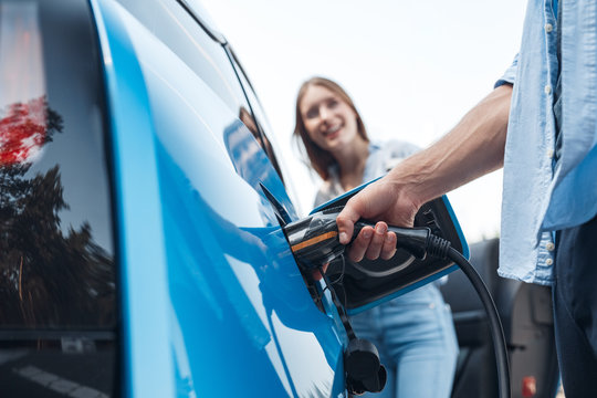 Young adult man charging blue electric car