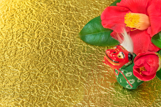 A Japanese greeting card with a Tsubaki flower also called the winter rose and an adorable Japanese Folklore animal figurine depicting a Shishimai lion on a golden crumpled paper.