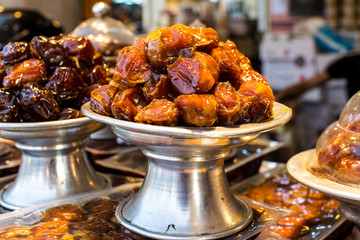Close Up Of Pile Of Dried Date Fruits In A Silver Metal Plate With Stand Exhibiting In The Shop during ramadan