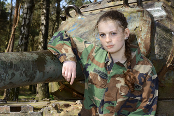 Girl in military army clothes with camouflage spots posing in front of a tank