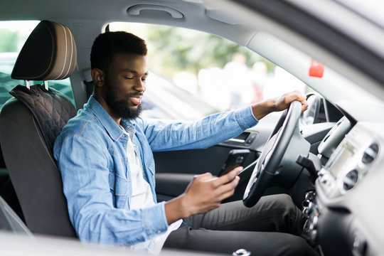 Young male African American holding his phone while drive his car