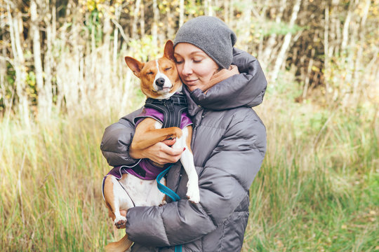 Woman is hugging and petting her cute basenji puppy while having walk in a nature side. Dog and his owner feeling happy together.