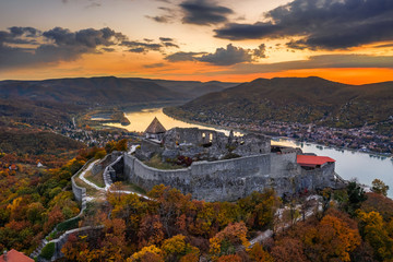 Visegrad, Hungary - Aerial drone view of the beautiful high castle of Visegrad with autumn foliage and trees. Dunakanyar and golden sunset at background Fototapete
