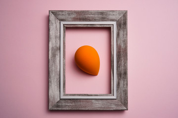 orange color blend beauty sponges on pink background with wooden frame. Makeup tool for applying and blending products such as foundation, concealer.