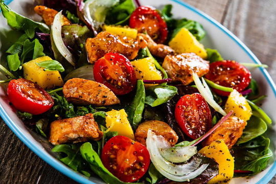 Salad with chicken, mango and tomatoes on wooden table